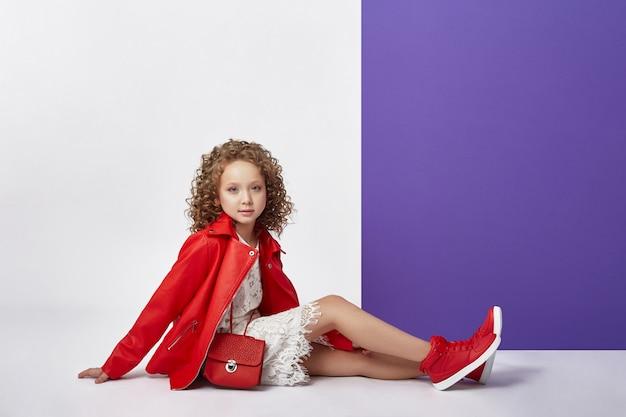 Moda dziewczyna w stylowe ubrania na kolorowym tle ściany. jasne jesienne ubrania dla dzieci