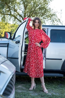 Moda dziewczyna w stylowej czerwonej sukience stojąca w pobliżu jej nowoczesnego samochodu i relaksująca natura
