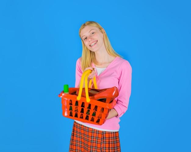 Moda dziewczyna z koszykiem na zakupy szczęśliwa dziewczyna na zakupach uśmiechnięta kobieta robi zakupy w supermarkecie