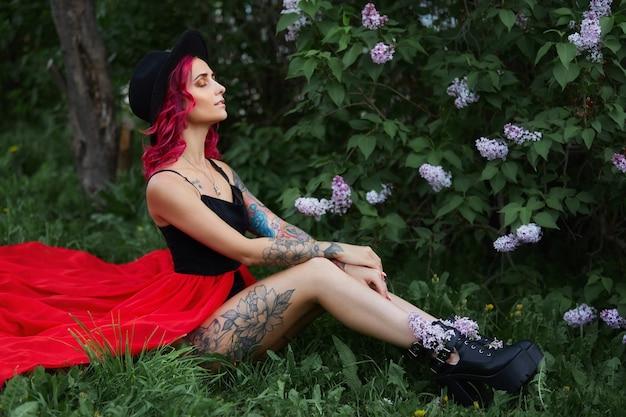 Moda dziewczyna z rudymi włosami i wielkim powołaniem kapelusz, portret wiosna w liliowym kolorze w lecie. piękna czerwona różowa sukienka, tatuaże na ciele kobiety. jasny makijaż, profesjonalna koloryzacja włosów