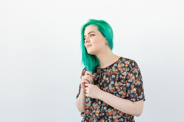 Moda, farbowanie włosów i koncepcja ludzi - portret pięknej dziewczyny z zielonymi włosami na białym