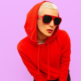 Moda hipster dziewczyna w czerwonej bluzie z kapturem i okularami przeciwsłonecznymi w miejskim stylu