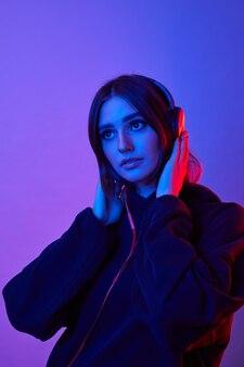 Moda hipster kobieta nosi słuchawki, słuchając muzyki na kolorowej ścianie neonu