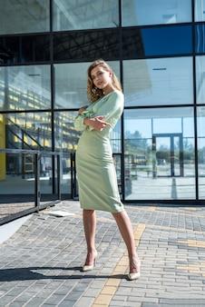 Moda i szczęśliwa kobieta w sukni stojącej przed nowoczesną architekturą szkła