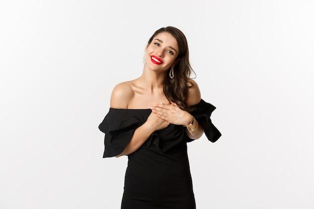 """Moda i uroda. atrakcyjna glamour kobieta w czarnej sukience, mówiąca """"dziękuję"""", uśmiechająca się i trzymająca ręce na sercu z zadowolonymi emocjami, białe tło"""