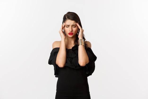 Moda i uroda. młoda nowoczesna kobieta w czarnej sukni, czerwona szminka, bóle głowy, dotykanie głowy i mdłości, stojąc na białym tle.