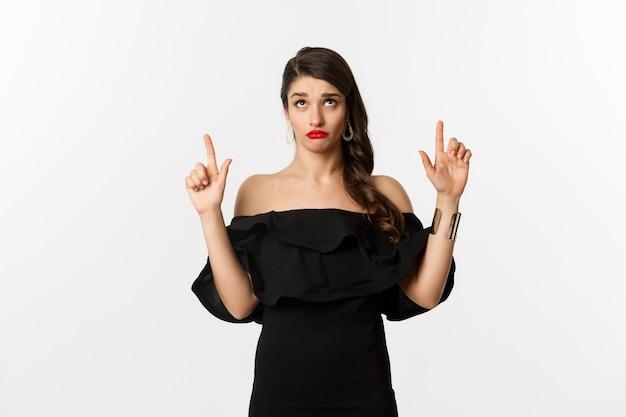 Moda i uroda. niemądra kobieta w czarnej sukience, czerwonych ustach, patrząca i wskazująca palce w górę z nierozbawionym, wątpliwym wyrazem twarzy, białe tło