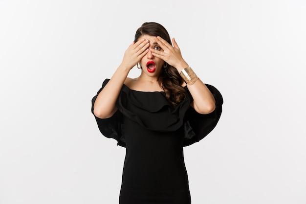Moda i uroda. obraz zszokowanej kobiety w czarnej sukience, zasłaniającej oczy, ale zerkającej przez palce zaskoczone, stojącej na białym tle