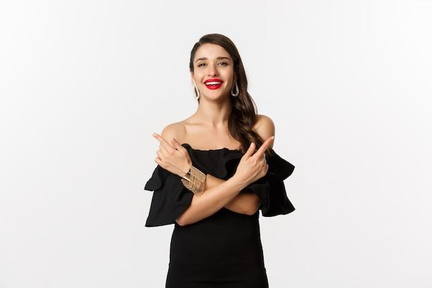 Moda i uroda. piękna kobieta szczęśliwa, wskazując bokiem, pokazując dwie możliwości i uśmiechając się, ubrana w czarną sukienkę, białe tło.