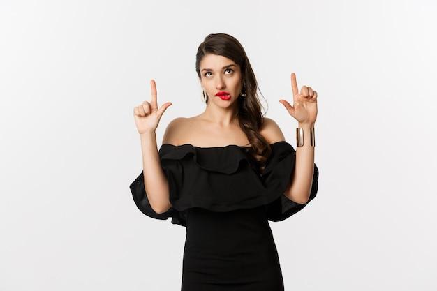 Moda i uroda. przemyślana atrakcyjna kobieta w czarnej sukni, patrząca i wskazująca w górę, myśląca z kuszącym spojrzeniem, białe tło