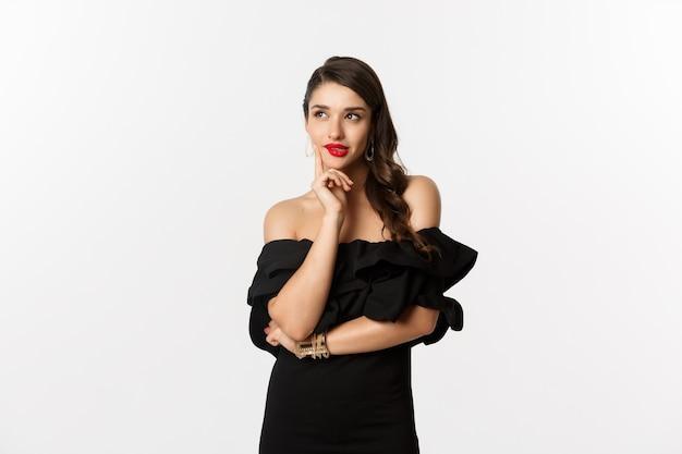 Moda i uroda. przemyślana młoda kobieta w czarnej sukni, uśmiechnięta zadowolona i myśląca, mając pomysł, białe tło.