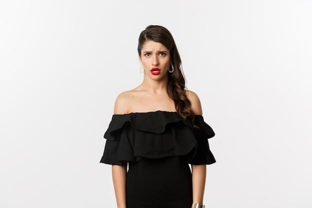 Moda i uroda. rozczarowana i zdenerwowana kobieta w czarnej sukni patrząca w kamerę niezadowolona, narzekająca z zazdrosnym spojrzeniem, stojąca na białym tle.