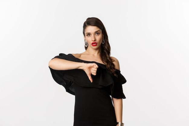 Moda i uroda. rozczarowana pyskata kobieta w czarnej sukience, pokazująca kciuki w dół, nie lubi czegoś złego, sądząc po białym tle.
