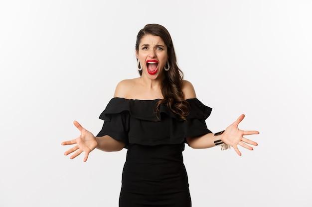 Moda i uroda. rozzłoszczona kobieta w czarnej sukience, krzycząca wściekła i ściskająca ręce, krzywiąc się oburzona przed kamerą, stojąc nad białym tłem.