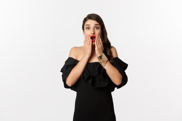 Moda i uroda. wizerunek modelki w czarnej sukni reagującej na ogłoszenie, patrząc zdziwiony na aparat, stojąc zaskoczony na białym tle.