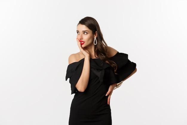 Moda i uroda. wizerunek stylowej pięknej kobiety w czarnej sukience i makijażu, patrząc w lewo z pokusą, dotykając czerwonych ust, stojąc na białym tle.