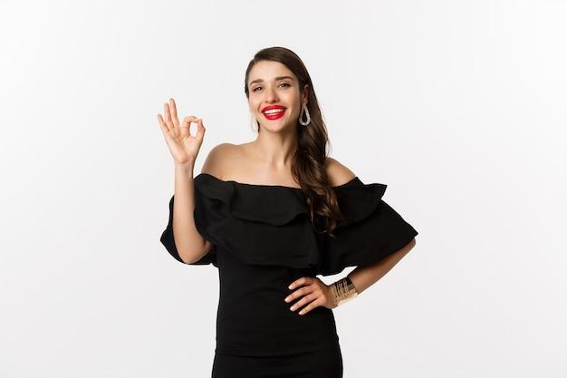Moda i uroda. zadowolona, przystojna kobieta z czerwoną szminką, czarną sukienką, okazywana na znak zgody, lubię i zgadzam się, stojąca na białym tle.