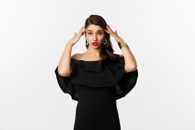 Moda i uroda. zirytowana i zmęczona kobieta w czarnej sukni, dotykająca głową i przewracająca oczami przeszkadzała, stojąc zdenerwowana na białym tle.
