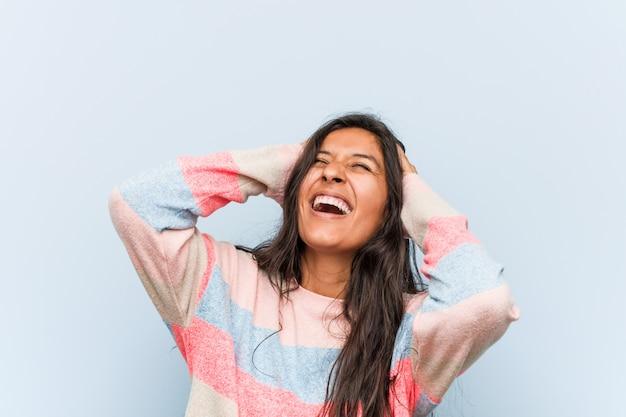 Moda indyjska młoda kobieta śmieje się radośnie trzymając ręce na głowie. koncepcja szczęścia.