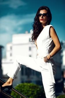 Moda kobieta dziewczyna model w białym garniturze w okulary na ulicy