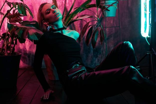Moda kobieta siedzi na podłodze w neonowym świetle tropikalnych liści. mokre włosy, idealna figura i makijaż. różowy i zielony neonowy kolor