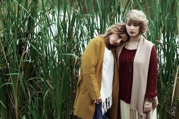 Moda kobiety pozują razem na świeżym powietrzu, jesienny park.