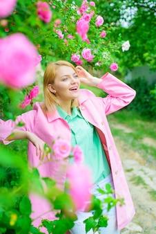 Moda kosmetyki perfumy kobieta w wiosennym parku piękna kobieta w pobliżu różowych róż w pięknym ogrodzie