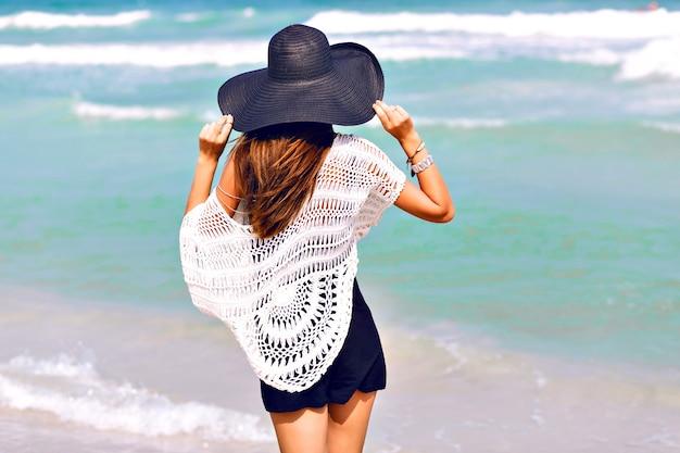 Moda lato wizerunek kobiety pozującej z powrotem, w pobliżu błękitnej wody morskiej, ładny słoneczny letni dzień, koniec relaksu ciesz się wolnością, radością, szczęściem, jasnymi kolorami