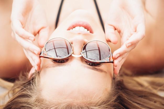 Moda letnia. dziewczyna w pobliżu basenu. seksowna kobieta w modnych okularach przeciwsłonecznych i modnych strojach kąpielowych bikini i ciesząc się luksusowe wakacje w hotelu resort.