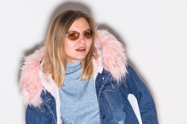Moda, ludzie i koncepcja miejskiego stylu zimy - młoda kobieta w modne ubrania na białej ścianie.