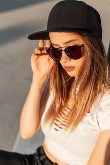 Moda łup młoda dziewczyna z ładnymi ustami w delikatnej skórze w stylowej czarnej czapce z daszkiem i modnych okularach przeciwsłonecznych na ulicy w niesamowity pomarańczowy zachód słońca. fajna nowoczesna kobieta na słońcu. portret z bliska.