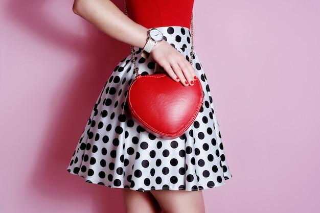Moda mała czerwona torebka w kształcie serca w dłoni dziewczyny. spódnica w biało-czarne groszki