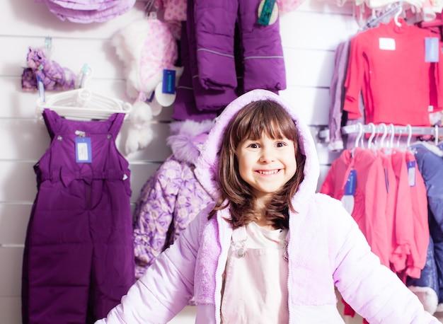 Moda mała dziewczynka założyła różową ciepłą kurtkę w sklepie odzieżowym