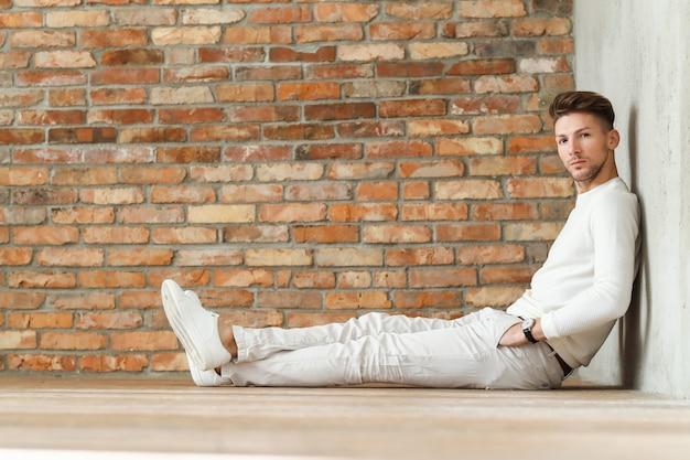 Moda męska na drewnianej podłodze, młody mężczyzna pozowanie