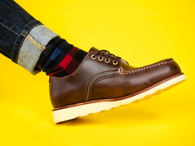 Moda męska z brązowymi butami ze skóry i dżinsami na żółtym tle.