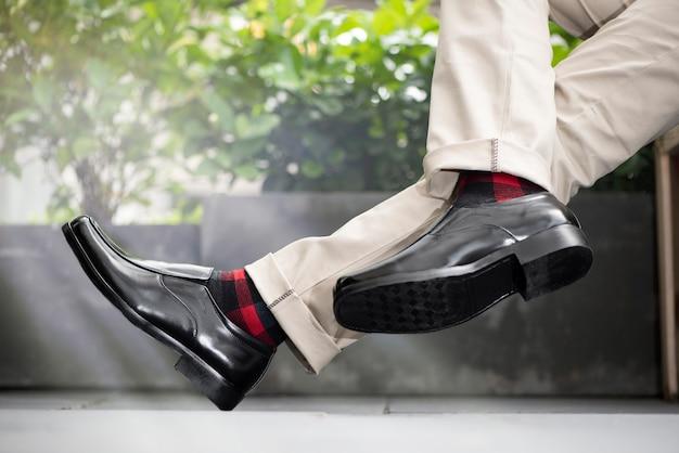 Moda mężczyzna nosi czarne skórzane buty
