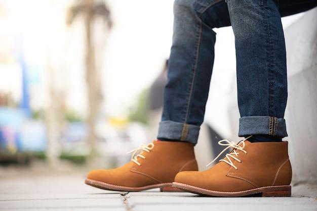 Moda mężczyzna nosi dżinsy i brązowe buty