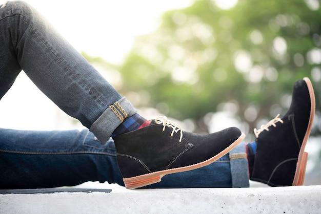 Moda mężczyzna nosi dżinsy i czarne buty