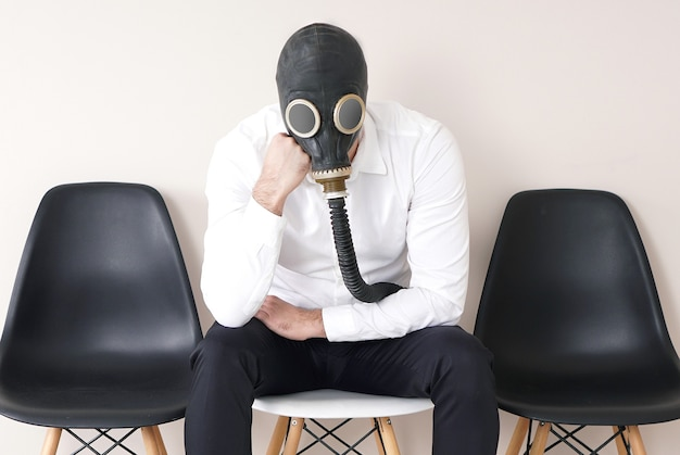 Moda mężczyzna w masce gazowej siedzi na krześle w pustym korytarzu.