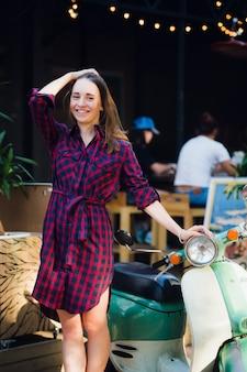 Moda miejska. plenerowy portret jest ubranym w kratkę suknię stoi blisko hulajnoga przy parkiem outdoors ładna młoda kobieta
