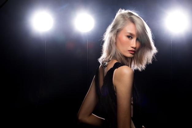 Moda młoda cienka kobieta azji tan skóry oczy piękny makijaż moda strój akcesoria pozowanie atrakcyjny wygląd glam. oświetlenie studyjne ciemne tło dym mgła tylna obręcz światła niska ekspozycja