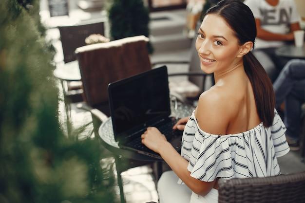 Moda młoda dziewczyna siedzi w letniej kawiarni