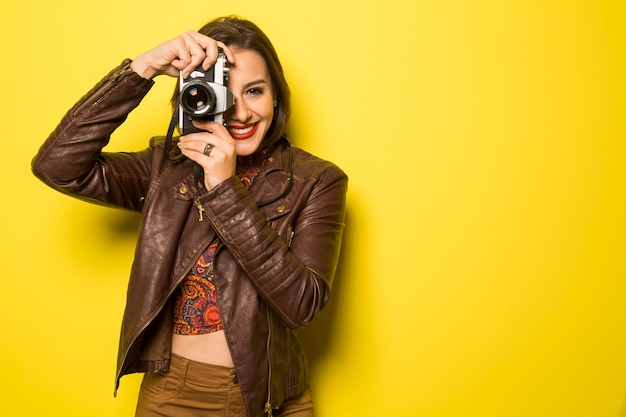 Moda młoda kobieta sprawia, że zdjęcie ze starym aparatem na żółtej ścianie