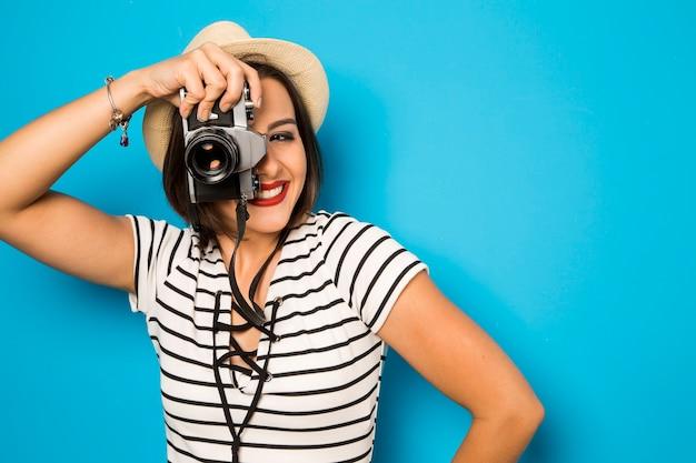 Moda młoda kobieta sprawia, że zdjęcie ze starym aparatem