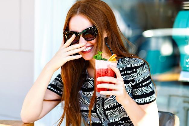 Moda młoda kobieta z długimi włosami i niesamowitym uśmiechem, trzymając smaczną słodką letnią lemoniadę koktajlową, elegancką sukienkę i makijaż, relaksując się w miejskiej kawiarni. szczęśliwe radosne emocje.