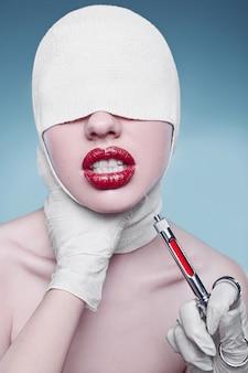 Moda młoda kobieta z zabandażowaną głową i wtryskiwaczem