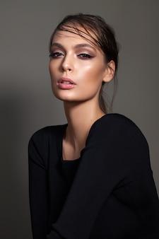 Moda młoda modelka z liliowym i szarym profesjonalnym makijażem, mokrą fryzurą, idealną skórą