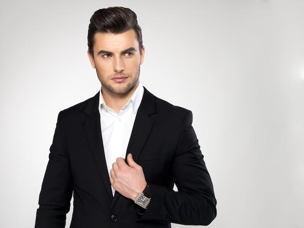 Moda młody biznesmen czarny garnitur dorywczo pozuje w studio