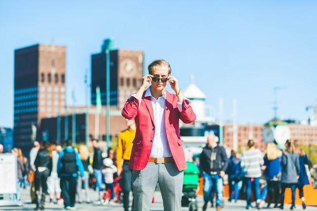 Moda młody człowiek w oslo obniżanie okularów przeciwsłonecznych