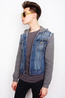 Moda młody człowiek z modnymi okularami przeciwsłonecznymi na białym tle